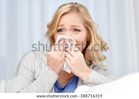 health care, flu, hygiene and people concept - ill woman blowing nose to paper napkin