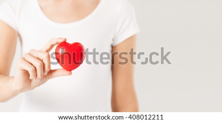 health care, medicine and charity concept - close up of woman holding red heart