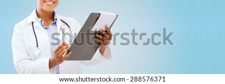 health care, people and medical concept - close up of smiling african american female doctor pointing finger to blank paper sheet on clipboard over blue background - stock photo