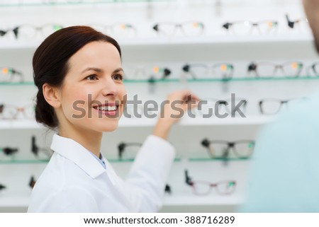 health care, people, eyesight and vision concept - female optician showing glasses to man at optics store - stock photo