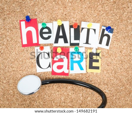 Health Care, pinned on cork bulletin board, stethoscope beside. - stock photo