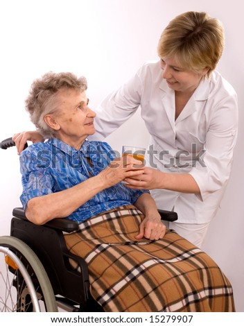 Health care worker and elderly woman in wheelchair needs help - stock photo