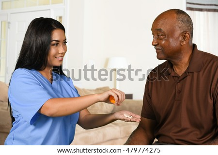 Health care worker helping an elderly patient take his pills