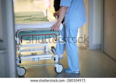 Health care worker pushing hospital mobile bed - stock photo