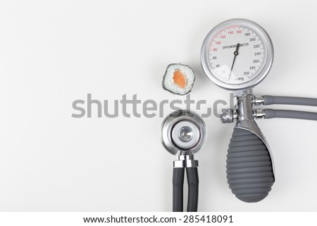 Health checkup with blood pressure gauge and stethoscope, sushi
