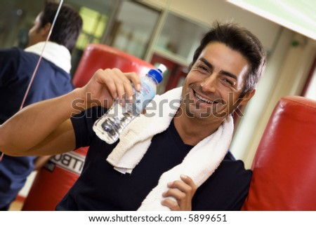 health club: athlete relaxing and drinking some water - stock photo
