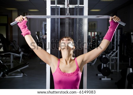 health club: girl in a gym doing weight lifting - stock photo