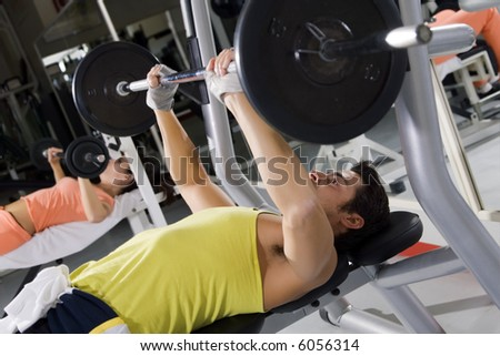 health club: guy in a gym doing weight lifting - stock photo