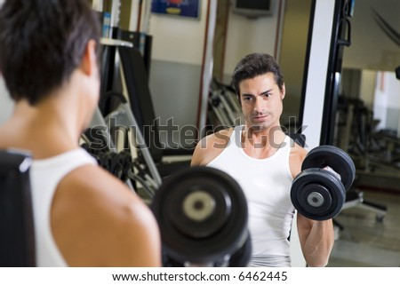 health club: guy in a gym doing weight lifting at the mirror - stock photo