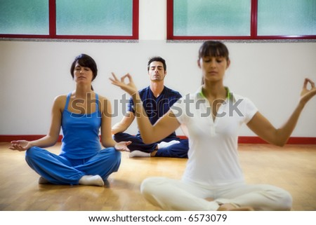 health club: man and women doing yoga - stock photo