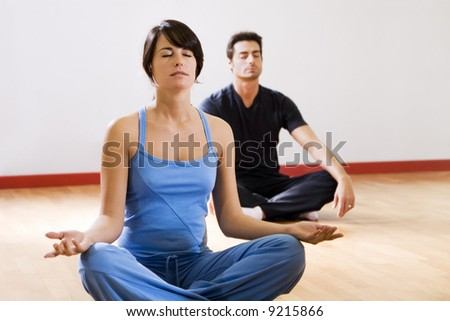 health club: man and women doing yoga. - stock photo