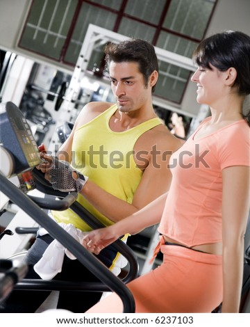 health club: woman walking on a tapis roulant with her personal trainer - stock photo