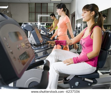 health club: women in the gym with their personal trainer - stock photo