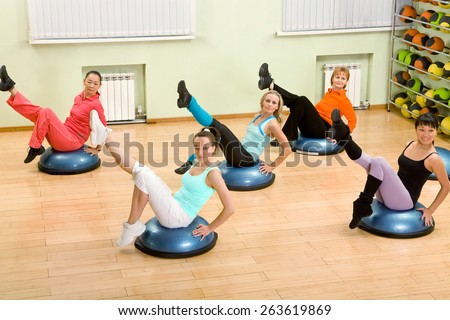 Health Club: Women of Different Age (from 18 to 50) Doing Step Aerobics in the Gym - stock photo