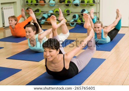 Health Club: Women of Different Age (from 18 to 50) Practicing Yoga in the Gym - stock photo