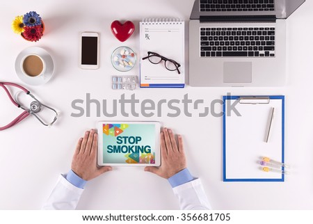 Health Concept-Doctor using tablet and showing STOP SMOKING - stock photo