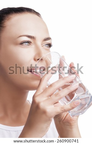Health Concept: Portrait of Happy Smiling Caucasian Brunette Woman Drinking Clear Water from Glass. Isolated Over Pure White Background. Vertical Image