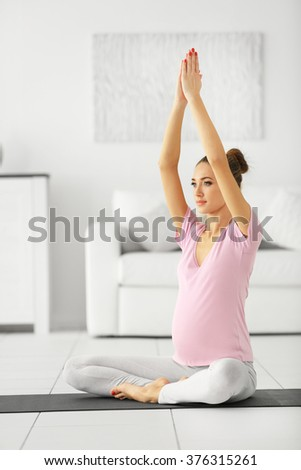 Health concept. Young beautiful pregnant woman does yoga exercise in the modern room - stock photo