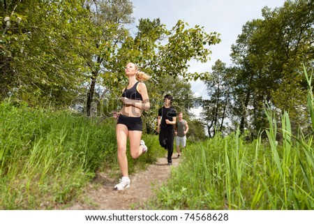 Health conscious people running on pathway - stock photo