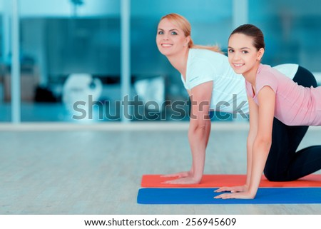Health conscious. Side view image of beautiful teenage girl and her mother in sports clothing training yoga on the mat in sports club  - stock photo