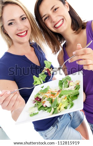 Health conscious women enjoying salad Two attractive happy casual young health conscious friends enjoying a green salad eating off a shared plate - stock photo