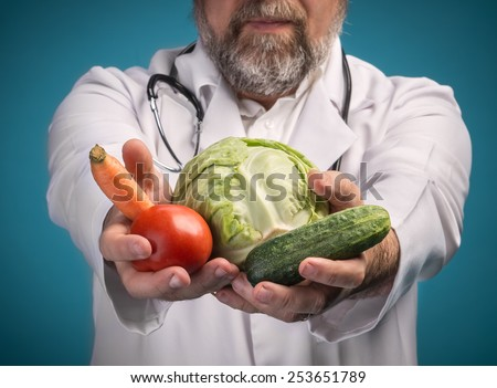 Health food concept. Doctor holding vegetables for healthy eating and healthy lifestyle. Focus on vegetables - stock photo