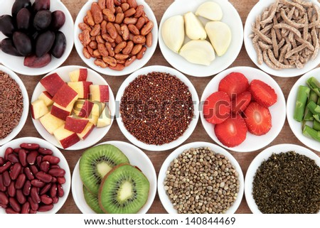 Health food ingredients in white porcelain bowls over papyrus background. - stock photo