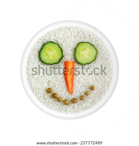 Health food - rice with vegetable smiling face - eyes cucumber, carrot nose, mouth green peas in circle isolated on white background - stock photo
