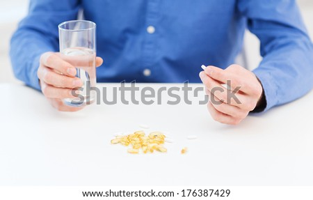 health, healthcare, medicine, medication, drugs, concept - close up of male hand holding pill and glass of water - stock photo