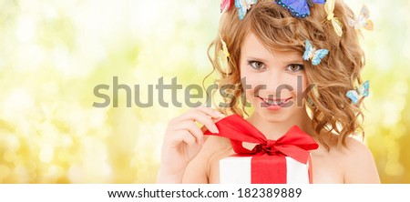 health, holidays and beauty concept - happy teenage girl with butterflies in hair opening gift box - stock photo