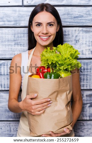 Health in her hands. Beautiful young woman in apron holding paper shopping bag full of fresh vegetables and smiling while standing in front of wooden background - stock photo