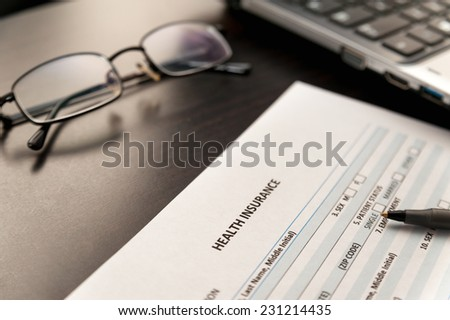 Health insurance application form on a wooden table with laptop computer and glasses - stock photo