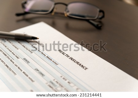 Health insurance application on a wooden table with glasses - stock photo