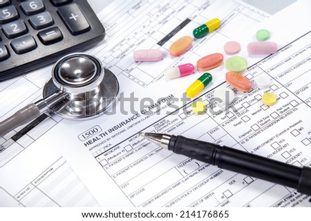 Health insurance concept. Stethoscope, health insurance form, pen, glasses, and calculator. - stock photo
