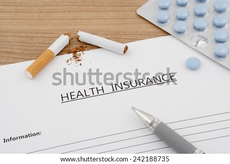 health insurance document with pills and broken cigarette on wooden table - stock photo
