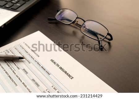 Health insurance form on a wooden table - stock photo