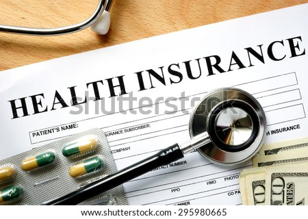 Health insurance form with stethoscope and pills.