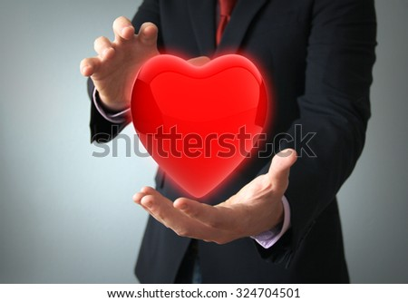 health insurance or love concept concept: hearth with electro on the hands of a businessman - stock photo