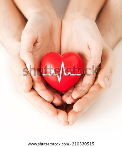 health, medicine and charity concept - closeup of couple hands holding red heart with ecg line - stock photo