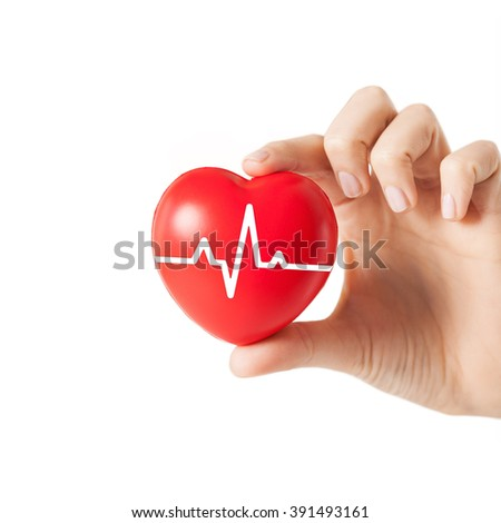 health, medicine, people and cardiology concept - close up of hand with cardiogram on small red heart - stock photo