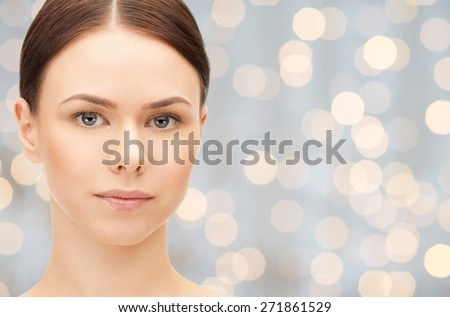 health, people and beauty concept - beautiful young woman face over holidays lights background - stock photo