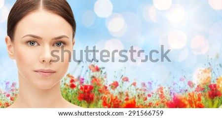 health, people and beauty concept - beautiful young woman face over poppy field background - stock photo
