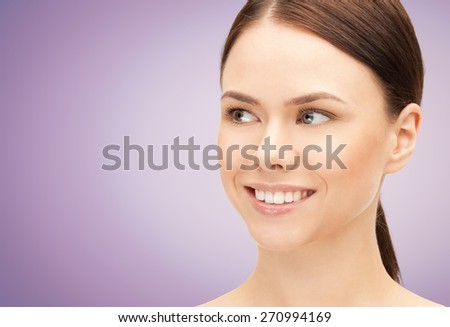 health, people and beauty concept - beautiful young woman face over violet background - stock photo