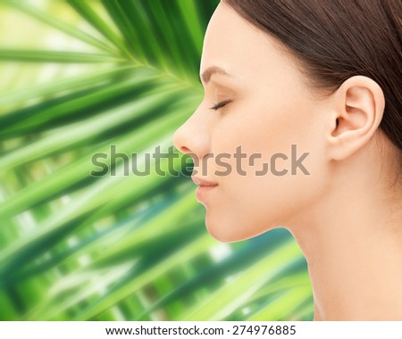 health, people, eco and beauty concept - beautiful young woman face over green palm leaf background - stock photo