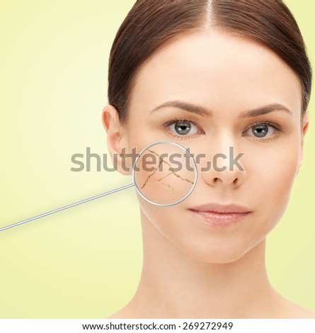 health, people, skin care and beauty concept - beautiful young woman face with dry dehydrated skin and magnifying glass over green background - stock photo
