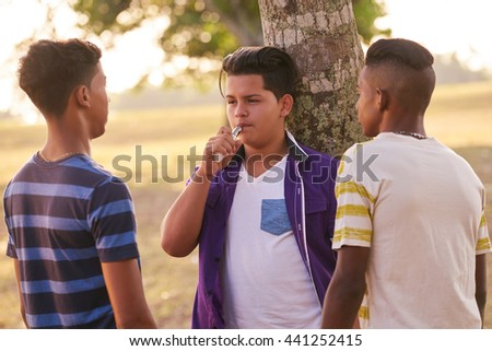 Health problems and social issues. Teenagers smoking electronic cigarette in park. - stock photo