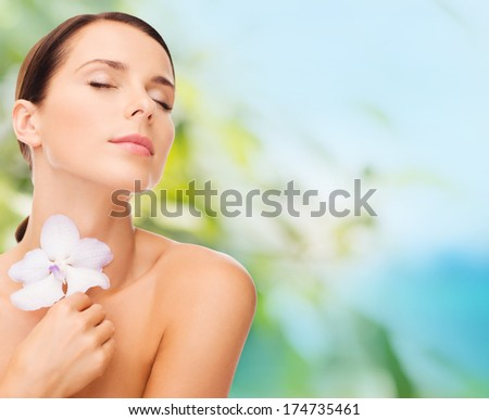 health, relaxation and beauty concept - relaxed woman with orhid flower