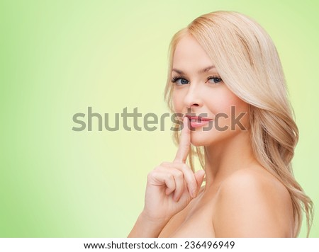 health, secret, people and beauty concept - clean face of beautiful young woman pointing finger to her lips over green background