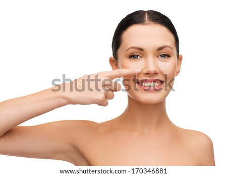 health, spa and beauty concept - clean face of beautiful young woman pointing to her cheek - stock photo