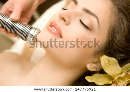 Health Spa: Close-up of Beautiful Relaxing Young Woman Having Facial Massage (electrolysis), with Orchid in Long Brown Hair - stock photo